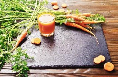 Closeup view at fresh organic vegetarian carrot juice on wooden