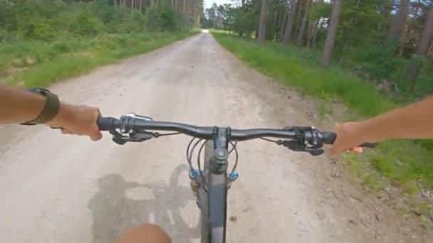 Jízda na štěrkovém horském kole na skalnaté cestě mezi zelenými poli. Pohled z pohledu první osoby Pov. 4k gimbal stabilizované video, Gopro Hero 7 černá.
