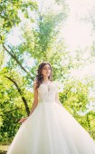 Gyönyörű fiatal menyasszony fehér esküvői ruha pózol park