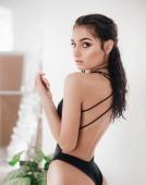 Beautiful young woman posing in black swimsuit