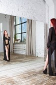 Girl in black lingerie and transparent peignoir is standing by the mirror
