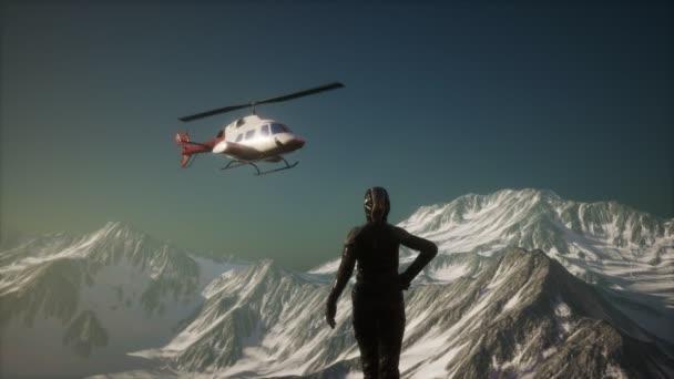 Frau und Hubschrauber in den winterlichen Bergen
