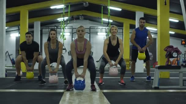 Strong muscular athletes working out training with kettlebells.