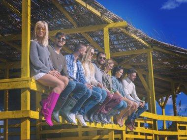 Mutlu bir arkadaş grubu yazlık evde takılıyor ve sonbahar günü bira içiyor. Renkli filtre.