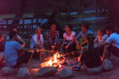 Bir grup mutlu genç arkadaş nehir kıyısında kamp ateşi etrafında dinleniyor ve eğleniyorlar.