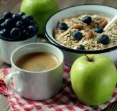 Zdravá snídaně je skvělý start do nového dne. Ovesné kaše, káva, jablko, jahody a ořechy na dřevěný stůl