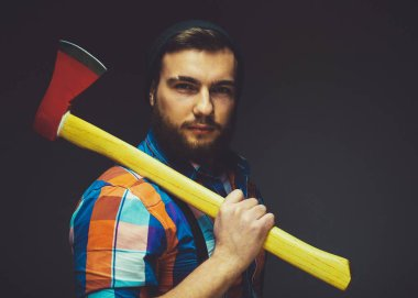 Brutal bearded male  holds an axe on his shoulder.