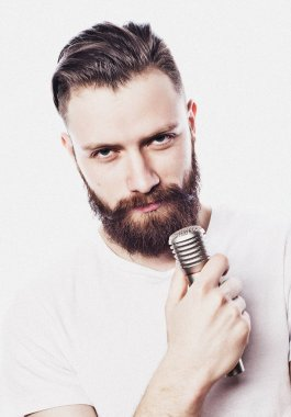 lifestyle and people concept: young bearded man singing with microphone