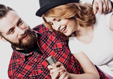 Lifestyle and people concept: Young couple with microphone