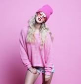 Stylové módní portrét módní příležitostné mladé ženy v růžové pulover a klobouk, vystupují nad růžové pozadí