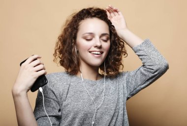 lifestyle and people concept: young woman in headphones listening to music smiling with closed eyes standing on beige background