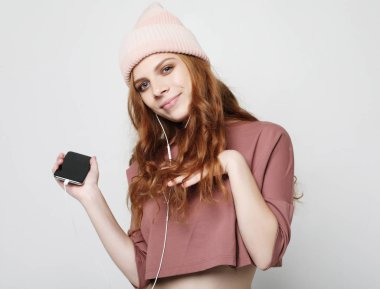 lifestyle and people concept: young woman in headphones with smartphone listening to the music.