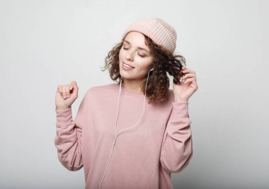 lifestyle and people concept: Beautiful young curly woman in headphones listening to music smiling with closed eyes