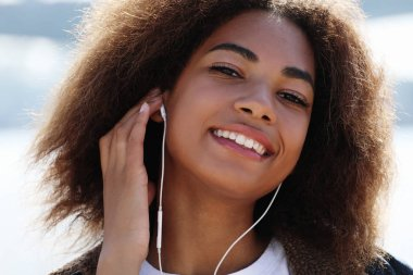 lifestyle concept: Young african american girl using mobile phone and headphones, smiling, close up