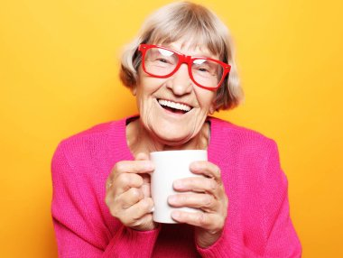 Portrait of old excited lady smiling laughing, holding cup drinking coffee, tea, beverage on yellow background