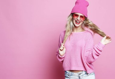 Stylish fashion portrait of trendy casual young woman in pink pulover and hat, posing over pink background.