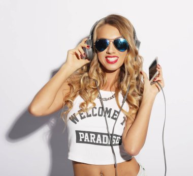 Portrait happy summer mood of joyful young woman with long curly hair listening to music