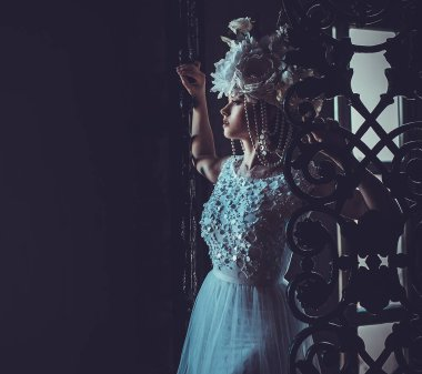 Elegant wedding dress and crown. Gorgeous young woman. Tender bride in a luxurious palace.
