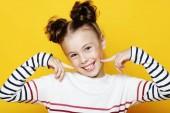Porträt eines fröhlich lächelnden kleinen Mädchens auf gelbem Hintergrund