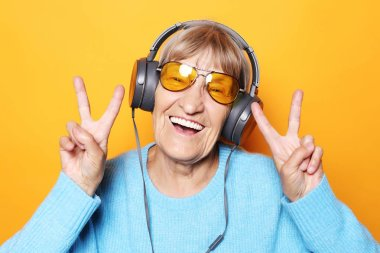Funny old lady listening music and showing thumbs up.