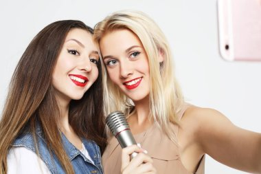 two beauty  girls with a microphone take selfie with smartphone