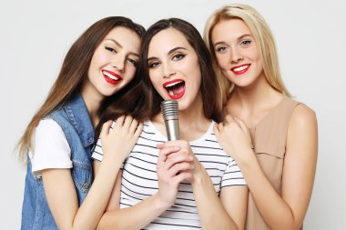 beauty girls with a microphone singing and having fun together