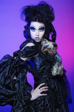 elegant dark queen with little dog over dark background