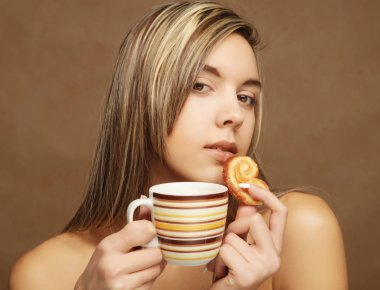 portrait of a beautiful young woman with a cup of coffee standing on the beige background