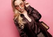 Krásná blondýnka v blůze a kalhoty nosí brýle, drží kabelku