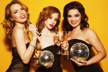 Three joyful charming young women with disco balls  drinking champagne and having fun together over yellow background stock vector