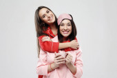 lifestyle, friendship and people concept - two beautiful girls dressed in pajamas hugging and smiling
