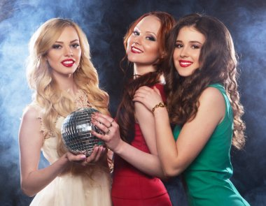 joyful charming young women with disco balls drinking champagne and having fun together