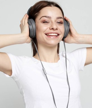 Beautiful young woman listening to music in headphones