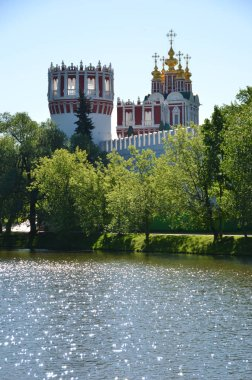 Novodevichiy Convent in green of trees by river under blue sky, Moscow