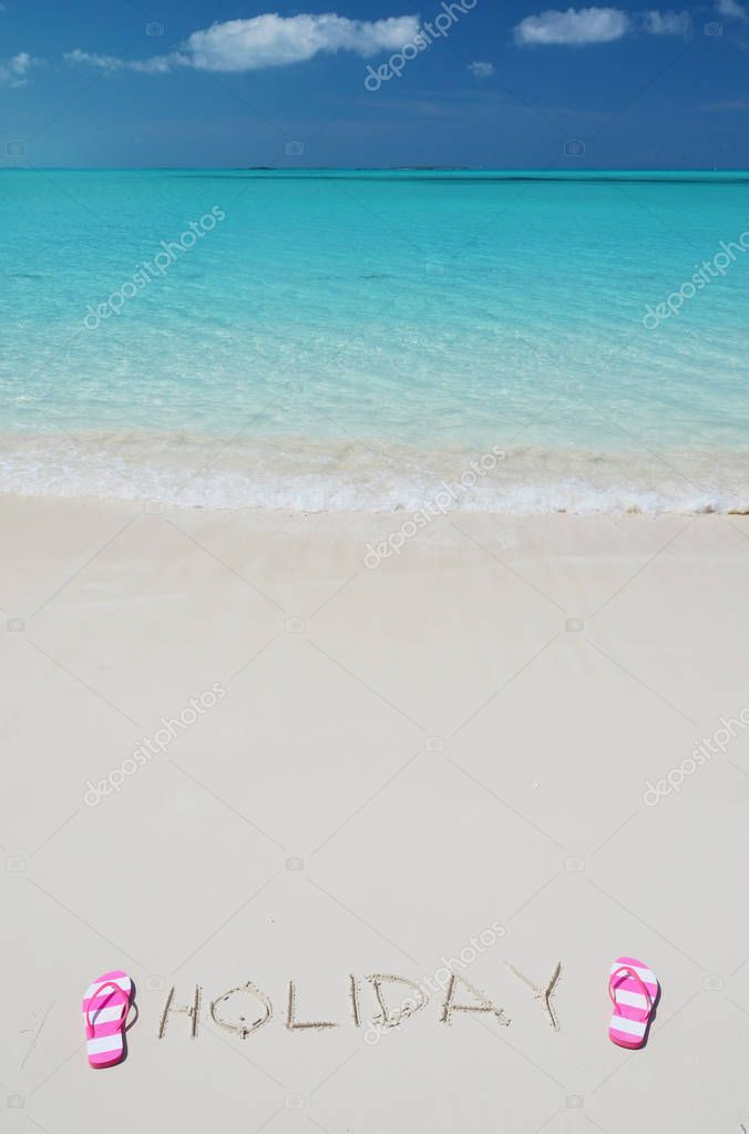 HOLIDAY writing on sandy beach with flip-flops near blue ocean water of Exuma, Bahamas