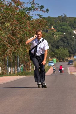 Young business man going to work with inline skate, alternative transport
