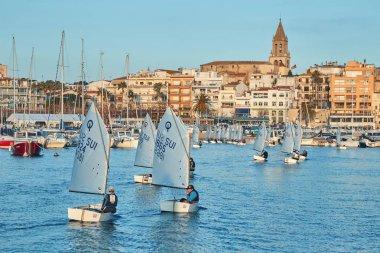 30th International Vila de Palamós Optimist Trophy, 14th Nations Cup. Sailboats sailing to the harbor small town Palamos in Spanish Costa Brava. 13. 02. 2019 Spain