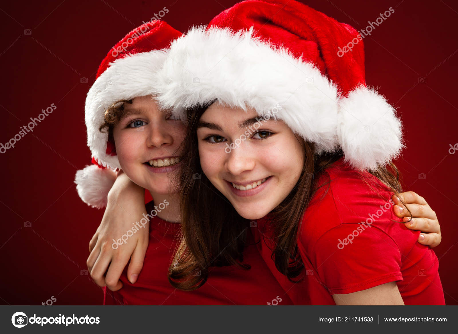 87894b974f6 Two kids in Santa hats hugging on gradient red and black background — Photo  by gbh007