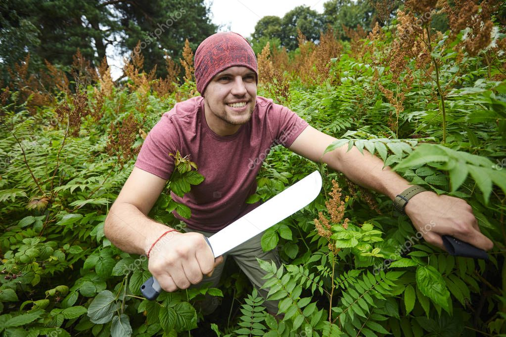 man with machete making his way through thicket