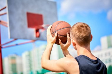 man holding ball while playing basketball outdoor