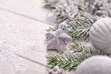 snowy Christmas tree branches with decorations on table background
