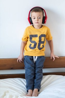 Boy in yellow t-shirt with headphones isolated on white background