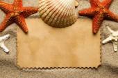 Nyári háttér – üres papír lapot és különböző lövedékek és tengeri csillag a homok