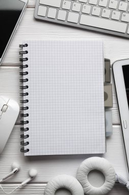 Notepad, headphones, smartphone and computer accessories on white wooden table