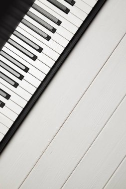 Piano keyboard on white woooden background