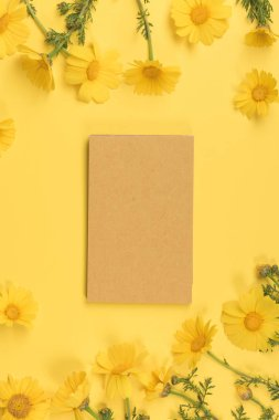 Flowers composition. Paper blank , chamomile flowers on yellow background. Spring, summer concept. Flat lay, top view, copy space