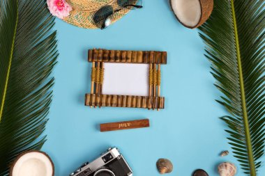Stylish summer composition with photo frame, green leaves, hat and sunglasses on a blue pastel background. Artwork mockup with copy space