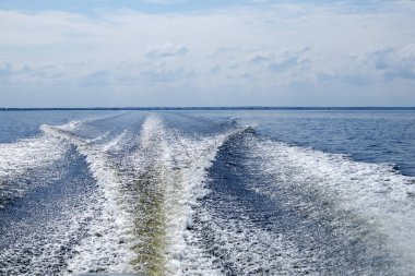 Large boat trail with foamy waves and sprays behind the fast motor boat