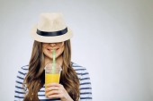 Fotografie funny portrait of smiling woman with hat on eyes drinking orange juice