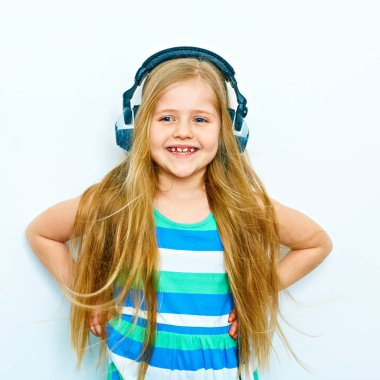 Little smiling blonde girl with long hair listening to  music with headphones. Isolated portrait.